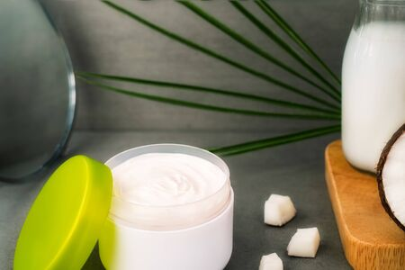 Close up opened cream for body skincare with coconut oil, fresh coconuts, palm leaf, bottle with coconut butter and mirror on dark gray background. Natural spa cosmetics concept.