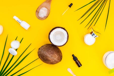 Top view organic natural cosmetics for face and body skincare with coconut oil on yellow background. Fresh coconuts and different cream containers and essential oil bottles with palm leaves. Flatlay.