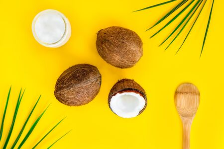 Top view organic bio coconut butter with two whole fresh coconuts, one half and palm leaves on yellow background. Natural oil for cooking and skincare beauty. Flatlay.