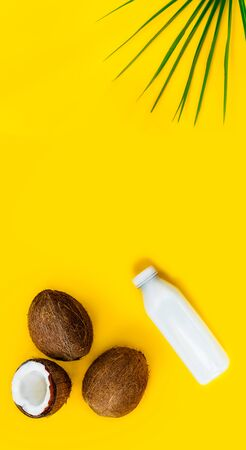 Top view bottle of fresh raw vegan coconut milk and fresh coconuts with a green palm leaf on the yellow background. Summer exotic refreshment. Natural plant based food. Vertical banner. Copy space