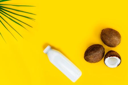 Top view bottle of fresh raw vegan coconut milk and fresh coconuts with a green palm leaf on the yellow background. Summer exotic refreshment. Natural plant based food. Copy space
