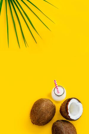 Top view coconut water drink, milk in bottle with straw, and fresh coconuts with a green palm leaf on the yellow background. Summer exotic refreshment. Natural plant based food. Vertical. Copy space