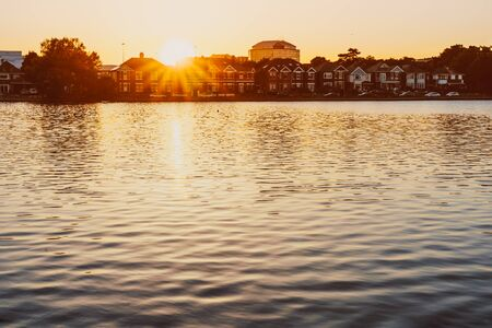 Peaceful lake view with small classic english houses under sunset light with sun beam. Cityscape. Copy space
