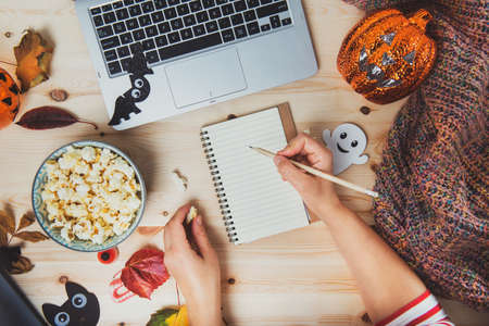 Top view woman writing plans or list of films for Halloween movie party. Blank notebook, laptop, popcorn bowl, pumpkin, bat, ghost, fall leaves, warm plaid on wooden background. Cozy and safe holiday.