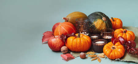 Orange, green decorative pumpkins, apples, nuts, fallen leaves and candles in autumn harvest composition on trendy earth tones background. Thanksgiving minimalism concept. Selective focus. Copy space