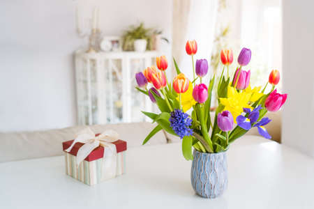 Fresh spring colorful bouquet of tulips, daffodils, irises in vase and gift box on white table with light classic design room background. Festive flowers for gift. Mockup for greeting card. Copy space.