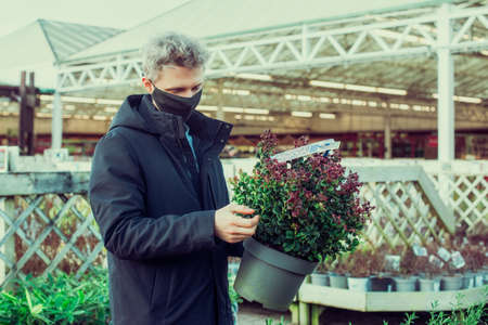 A young man in a protective face mask covering choosing a new green plant in an outdoor garden trading center. Preparing for the new spring planting season. Hobby and leisure time. Selective focus.