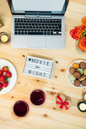 Top view Romantic Movie night concept. Movie night message on light board, laptop, candles, flowers, macaroons, berries, and two glasses with wine for belovers. Cozy holiday plans for Valentine's day