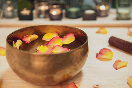 Tibetan singing bowl with floating in water flower petals. Special sticks, burning candles, petals on the wooden background. Meditation and Relax treatment. Exotic massage. Selective focus