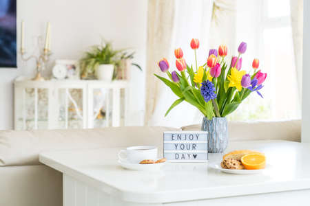 Good morning concept. Romantic breakfast - fresh spring flowers, cup of hot coffee drink, cookies, orange, lightbox with message Enjoy your day on marble table with light interior view. Copy space.