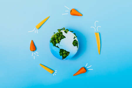 Creative veganism and Earth day concept. Rockets of carrots and baby corn flying around planet Earth. Earth model made of paper and fresh green sprouts collage on blue background. Save green planet.