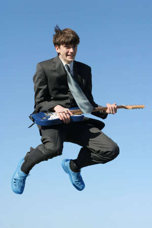 rockstars: young happy businessman with guitar jumping high