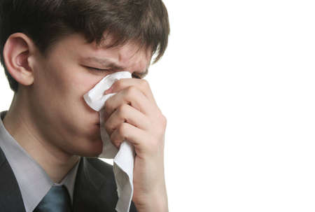 sniffles: ill young man with sad eyes and kleenex on his nose Stock Photo