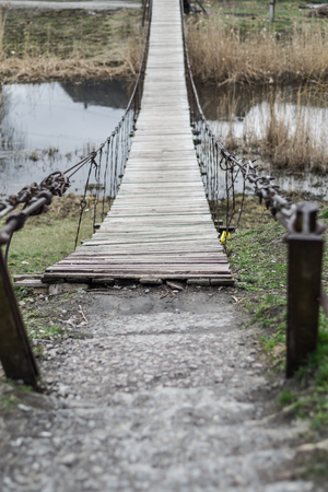 worn: Old wooden hanging bridge with metal cables across the river. Stock Photo