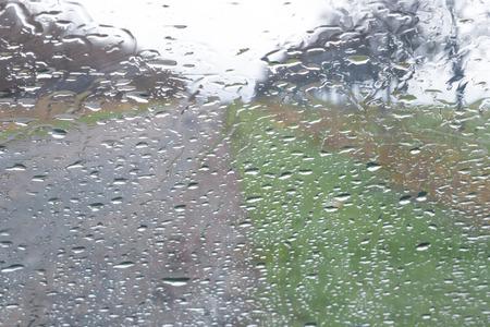 Rain drop on car front window, road view through window.