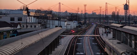 Railway tracks on train station at the sunset on the silhouette city background