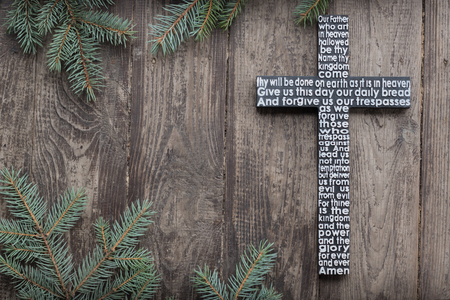 Old wooden cross with the Lords prayer on the shabby dark wooden plank with fir tree branches background
