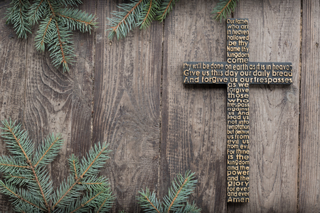 Black wooden cross with the Lord's prayer on the shabby dark wooden plank with fir tree branches background. Imagens
