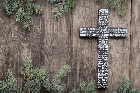 Wooden cross with the Lords prayer on the shabby dark wooden plank with fir tree branches background