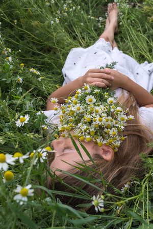 Beautiful little girl in a white dress is lying on a green meadow with a bouquet of daisies