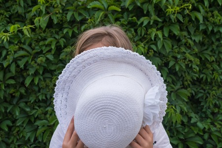 Little girl covers her face with a white hat on a green grape leaf background Foto de archivo