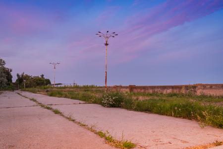Old abandoned sea promenade with lanterns beautiful evening sky background
