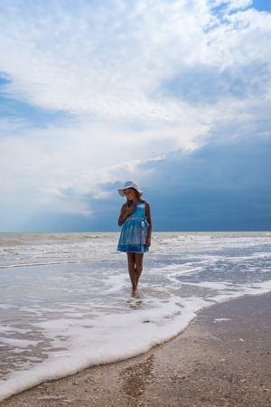 Beautiful seascape. Girl in dress and white hat on the beach over blue sky background