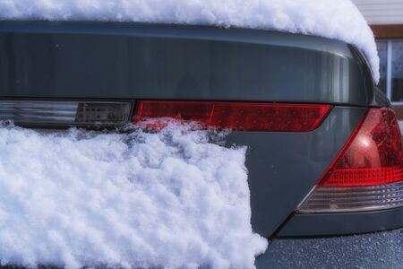 Close-up. Red taillight of a car under a layer of snow in winter