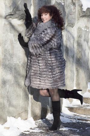 silver fox: La atractiva mujer en un abrigo de piel de zorro de plata de pie en una pared de piedra.