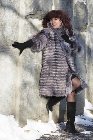 The attractive woman in a fur coat from the silver fox  standing at a stone wall. photo