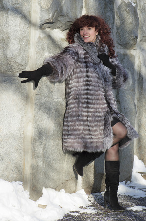 silver fox: The attractive woman in a fur coat from the silver fox  standing at a stone wall