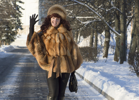 The attractive woman in a fox fur coat waves a hand  photo