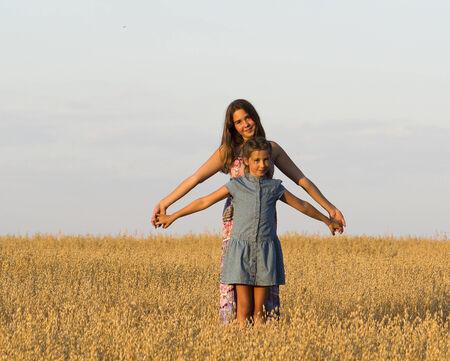 haver veld: Twee meisjes staat in haver veld.