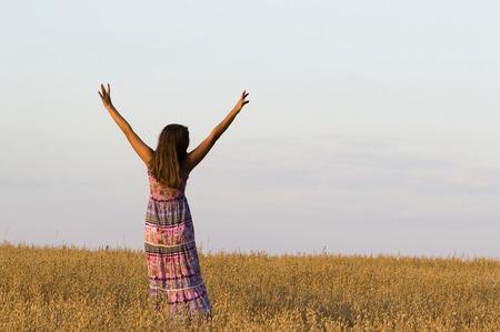 haver veld: Het meisje zet handen omhoog staan in haver veld. Stockfoto
