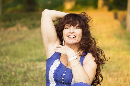 joyfully: The attractive middle age woman is sitting on a grass and joyfully smiles.