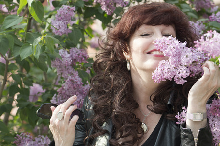 fervent: Outdoor portrait of the middle age woman beside a blossoming lilac tree.