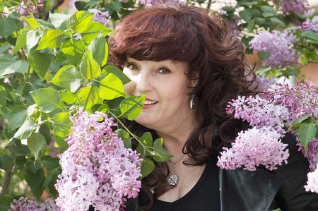 Ritratto esterno della donna di mezza età accanto a un albero lillà in fiore.