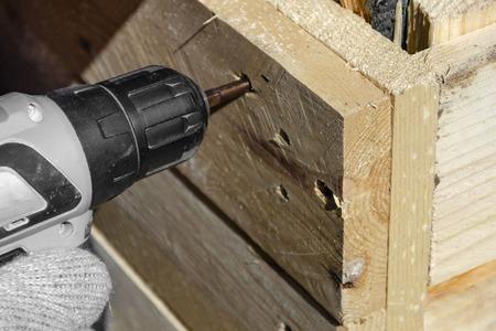 een man met een schroevendraaier schroeft een schroef in een houten product