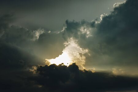 Sunset light breaks through thick dark clouds. Gloomy photo of the sky.