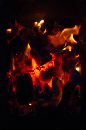 Brennende rote Kohlen im Dunkeln. Selektiver Fokus