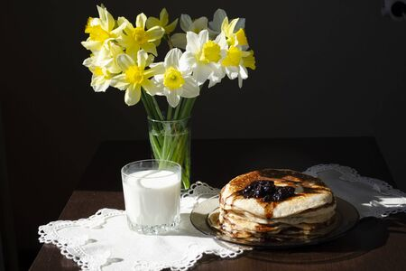Still life. A stack of pancakes with jam. A glass of milk. A bouquet of daffodils. Linen cloth
