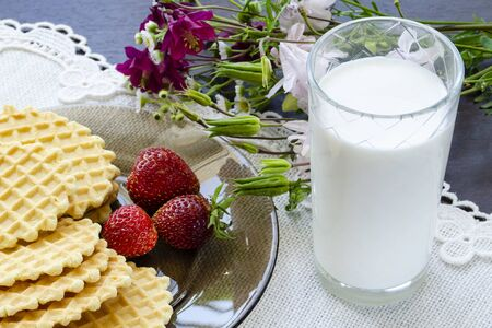 Breakfast of waffles and milk with strawberries on a rough woven napkin