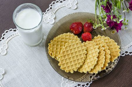 Crispy waffles on a plate and milk in a glass