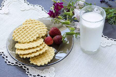 Crumbly waffles on a plate with strawberries and a glass of milk