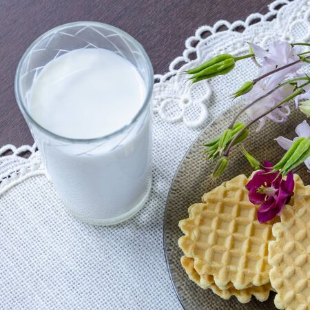 A glass of milk and a plate with waffles and flowers