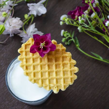 A glass of milk with a wafer and a flower. Selective focus3