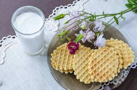 Waffles with aquilegia flowers and a glass of milk