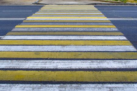 asphalt with yellow and white stripes at a pedestrian crossing
