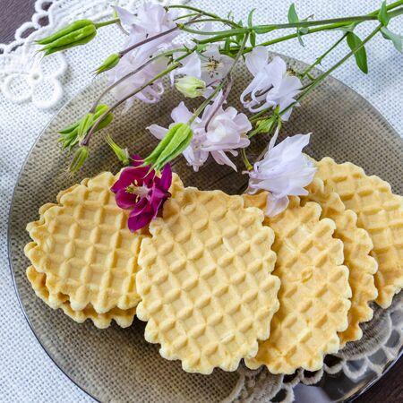 Crispy waffles on a plate and aquilegia flowers