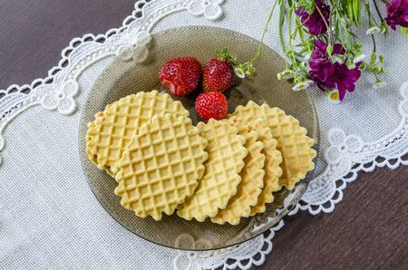 Crispy waffles with strawberries on a dark plate on a white napkin